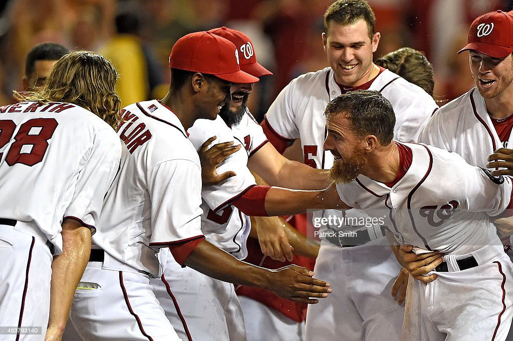 <a gi-track='captionPersonalityLinkClicked' href=/galleries/search?phrase=Adam+LaRoche&family=editorial&specificpeople=216533 ng-click='$event.stopPropagation()'>Adam LaRoche</a> #25 of the Washington Nationals is mobbed by teammates after hitting a walk-off solo home run against the Arizona Diamondbacks in the eleventh inning at Nationals Park on August 18, 2014 in Washington, DC. The Washington Nationals won, 5-4, in the eleventh inning.