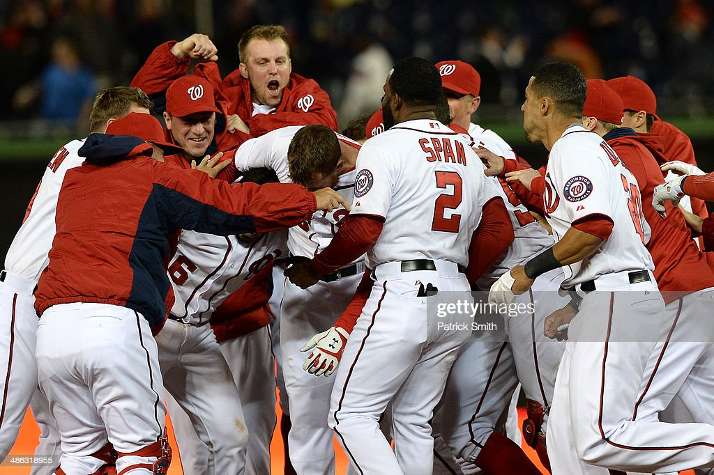Adam LaRoche #25 of the Washington Nationals is smothered by teammates after hitting an RBI single to win the game in the ninth inning against the Los Angeles Angels of Anaheim at Nationals Park on April 23, 2014 in Washington, DC. The Washington Nationals won, 5-4.