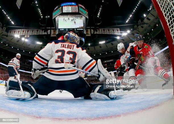 Adam Larsson of the Edmonton Oilers and Jonathan Toews of the Chicago Blackhawks battle for the puck next to goalie Cam Talbot at the United Center...