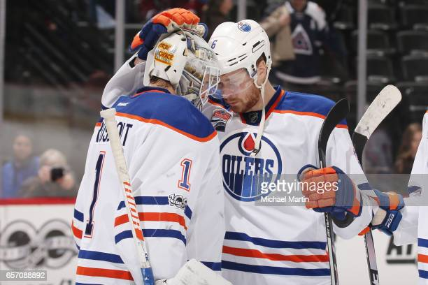 Adam Larsson of the Edmonton Oilers congratulates goaltender Laurent Brossoit after a win against the Colorado Avalanche at the Pepsi Center on March...
