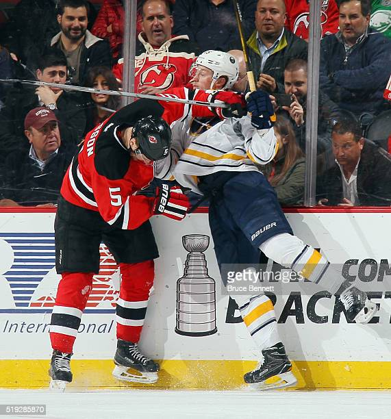 Adam Larsson of the New Jersey Devils checks Jack Eichel of the Buffalo Sabres into the boards during the second period at the Prudential Center on...