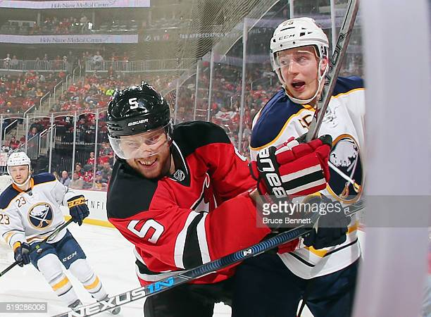 Adam Larsson of the New Jersey Devils checks Rasmus Ristolainen of the Buffalo Sabres into the glass during the second period at the Prudential...
