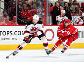 Adam Larsson of the New Jersey Devils controls the puck away from the defense of Jordan Staal during an NHL game at PNC Arena on December 26 2015 in...