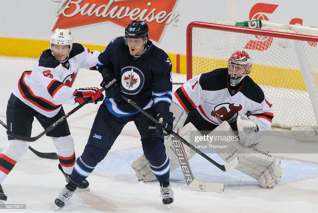 Adam Larsson #5 of the New Jersey Devils jostles with Nik Antropov #80 of the Winnipeg Jets as they set a screen in front of Devils goaltender Johan Hedberg #1 during second-period action at the MTS Centre on February 28, 2013 in Winnipeg, Manitoba, Canada. The Jets defeated the Devils 3-1.