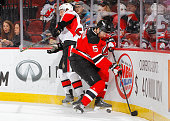 Adam Larsson of the New Jersey Devils wins the puck from Erik Condra of the Ottawa Senators during the first period at the Prudential Center on...