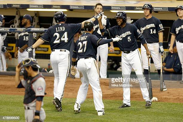 Adam Lind of the Milwaukee Brewers celebrates with Hector Gomez and Carlos Gomez a two run homer in the eighth inning against the Minnesota Twins...