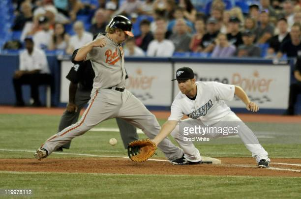 Adam Lind of the Toronto Blue Jays covers first base as Mark Reynolds of the Baltimore Orioles steps back to the bag during MLB game action July 27...