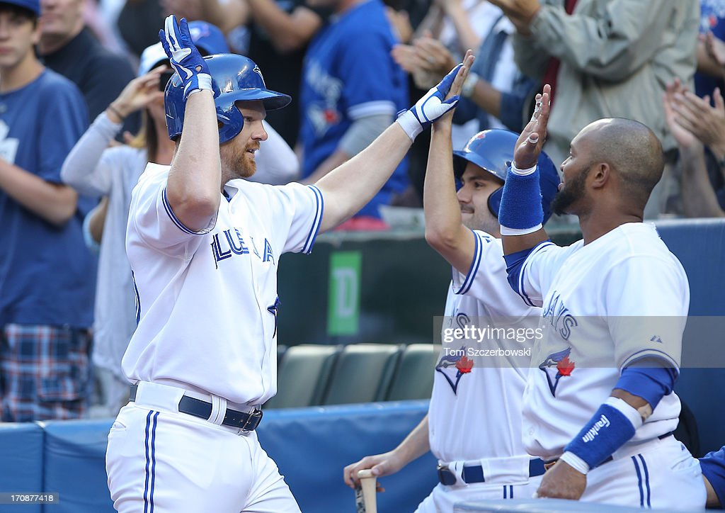 <a gi-track='captionPersonalityLinkClicked' href=/galleries/search?phrase=Adam+Lind&family=editorial&specificpeople=3911783 ng-click='$event.stopPropagation()'>Adam Lind</a> #26 of the Toronto Blue Jays is congratulated by <a gi-track='captionPersonalityLinkClicked' href=/galleries/search?phrase=Emilio+Bonifacio&family=editorial&specificpeople=4193706 ng-click='$event.stopPropagation()'>Emilio Bonifacio</a> #1 after hitting a 3-run home run in the first inning during MLB game action against the Colorado Rockies on June 19, 2013 at Rogers Centre in Toronto, Ontario, Canada.