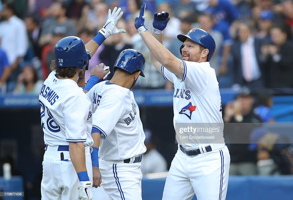<a gi-track='captionPersonalityLinkClicked' href=/galleries/search?phrase=Adam+Lind&family=editorial&specificpeople=3911783 ng-click='$event.stopPropagation()'>Adam Lind</a> #26 of the Toronto Blue Jays is congratulated by teammates after hitting a 3-run home run in the first inning during MLB game action against the Colorado Rockies on June 19, 2013 at Rogers Centre in Toronto, Ontario, Canada.