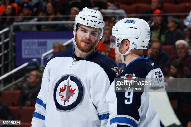 Adam Lowry and Andrew Copp of the Winnipeg Jets chat before a faceoff during the game against the Anaheim Ducks on March 24 2017 at Honda Center in...