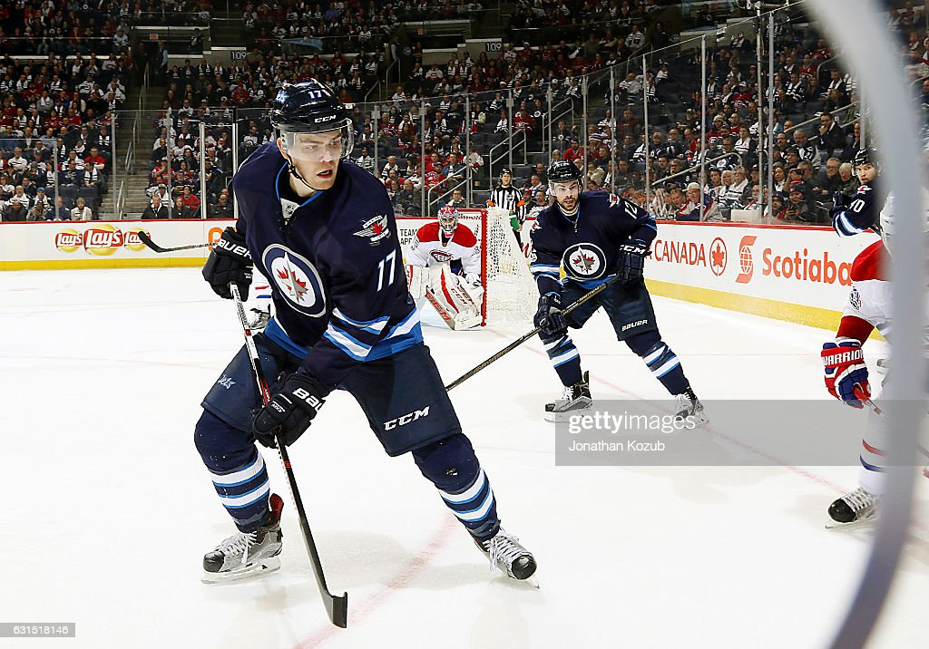 Adam Lowry #17 and Drew Stafford #12 of the Winnipeg Jets keep an eye on the play along the boards during third period action against the Montreal Canadiens at the MTS Centre on January 11, 2017 in Winnipeg, Manitoba, Canada.