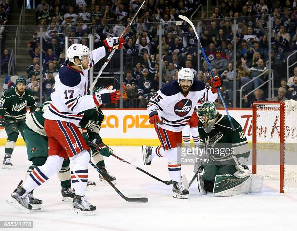 Adam Lowry and Mathieu Perreault of the Winnipeg Jets celebrate a first period goal against the Minnesota Wild at the MTS Centre on March 19 2017 in...
