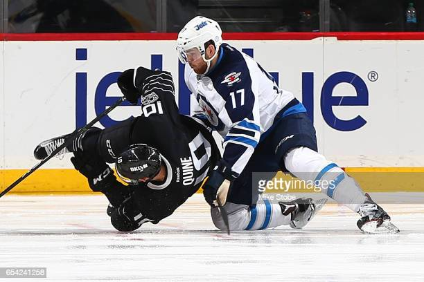 Adam Lowry of the Winnipeg Jets and Alan Quine of the New York Islanders get tangled up at the Barclays Center on March 16 2017 in Brooklyn borough...