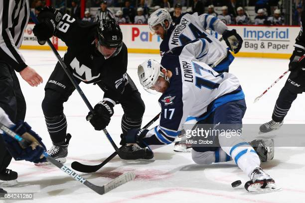Adam Lowry of the Winnipeg Jets and Brock Nelson of the New York Islanders battle for the puck at the Barclays Center on March 16 2017 in Brooklyn...