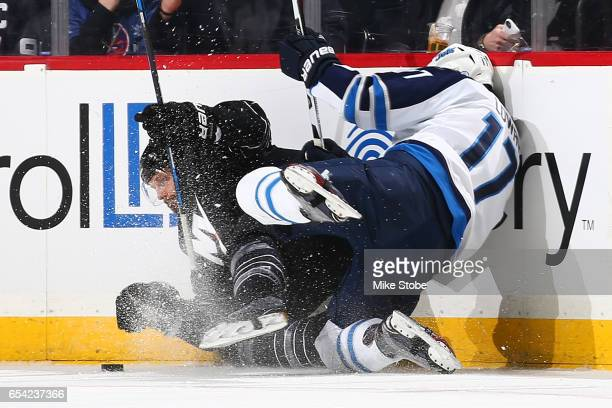 Adam Lowry of the Winnipeg Jets and Dennis Seidenberg of the New York Islanders fall to the ice battling for the puck at the Barclays Center on March...