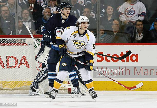 Adam Lowry of the Winnipeg Jets and Kevin Fiala of the Nashville Predators keep an eye on the play at the point during second period action at the...