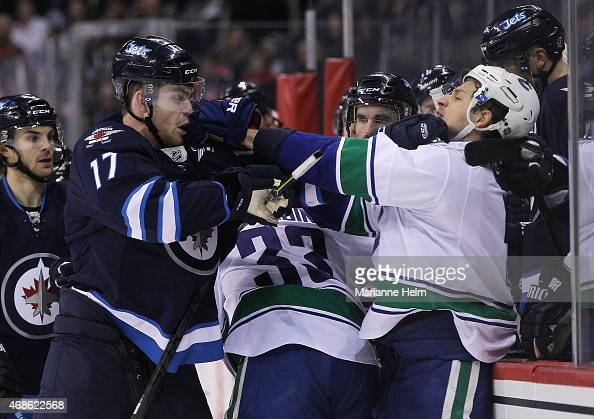 Adam Lowry of the Winnipeg Jets and Luca Sbisa of the Vancouver Canucks shove each other during second period action in an NHL game at the MTS Centre...