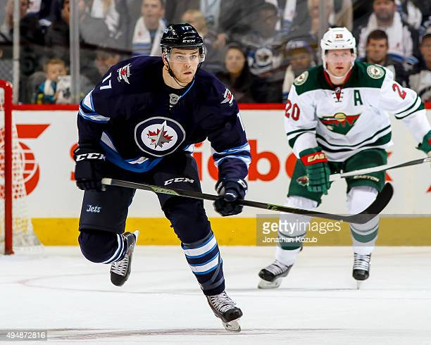 Adam Lowry of the Winnipeg Jets and Ryan Suter of the Minnesota Wild follow the play down the ice during first period action at the MTS Centre on...