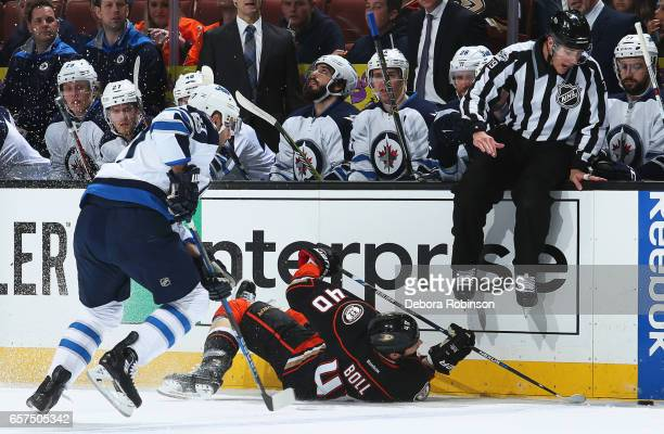 Adam Lowry of the Winnipeg Jets battles for the puck against Jared Boll of the Anaheim Ducks during the game on March 24 2017 at Honda Center in...