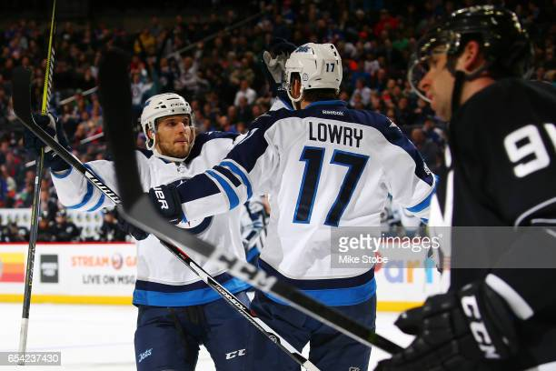Adam Lowry of the Winnipeg Jets celebrates his second period goal with Ben Chiarot as John Tavares of the New York Islanders looks on at the Barclays...