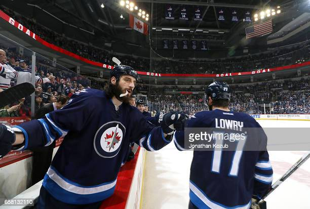 Adam Lowry of the Winnipeg Jets celebrates his third period goal against the Vancouver Canucks with teammate Chris Thorburn at the MTS Centre on...