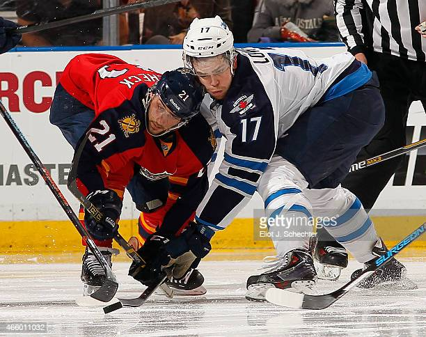 Adam Lowry of the Winnipeg Jets faces off against Vincent Trocheck of the Florida Panthers at the BBT Center on March 12 2015 in Sunrise Florida