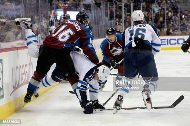 Adam Lowry of the Winnipeg Jets falls to the ice after missing a check on Nikita Zadorov of the Colorado Avalanche during the third period at the...