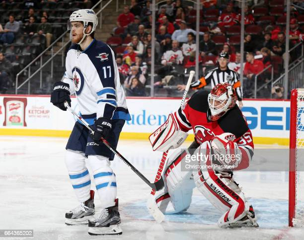 Adam Lowry of the Winnipeg Jets obstructs the view of Cory Schneider of the New Jersey Devils during the game on March 28 2017 at the Prudential...