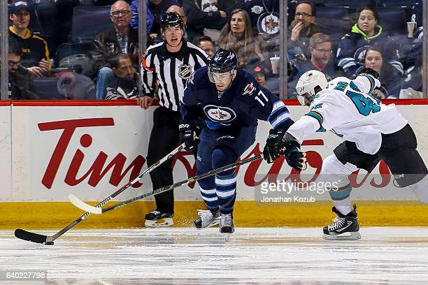 Adam Lowry of the Winnipeg Jets plays the puck down the ice as Joel Ward of the San Jose Sharks defends during second period action at the MTS Centre...