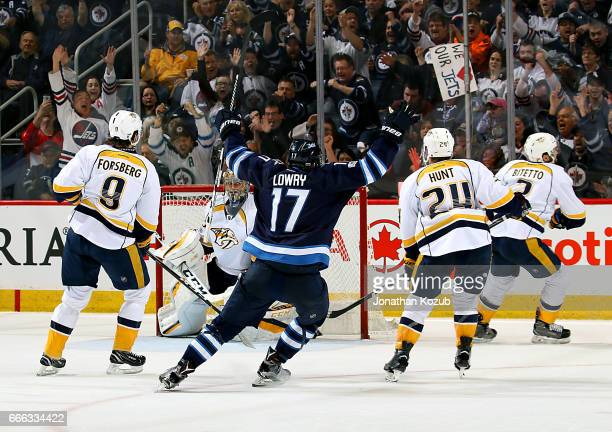Adam Lowry of the Winnipeg Jets raises his arms in celebration after teammate Kyle Connor scores a third period goal against the Nashville Predators...