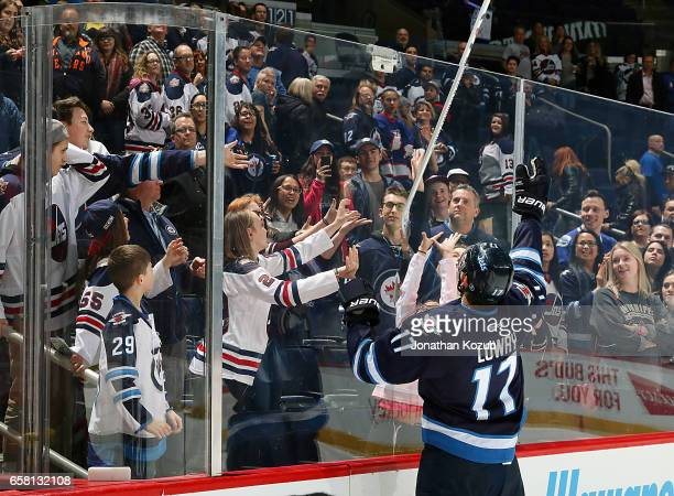 Adam Lowry of the Winnipeg Jets sends a souvenir stick over the glass to lucky fans after being named the second star of the game following a 21...