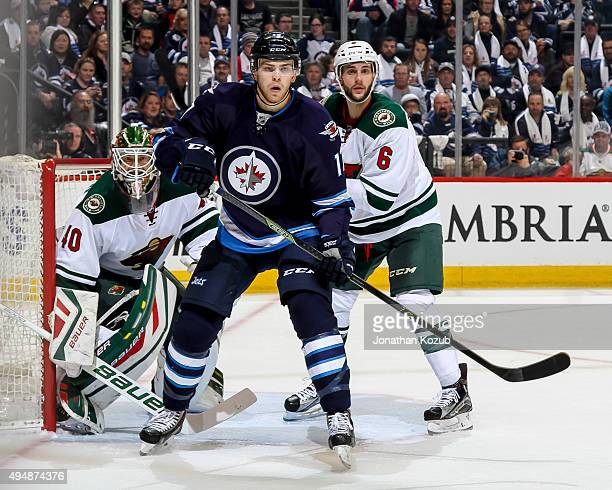 Adam Lowry of the Winnipeg Jets sets a screen in front of goaltender Devan Dubnyk and Marco Scandella of the Minnesota Wild during second period...