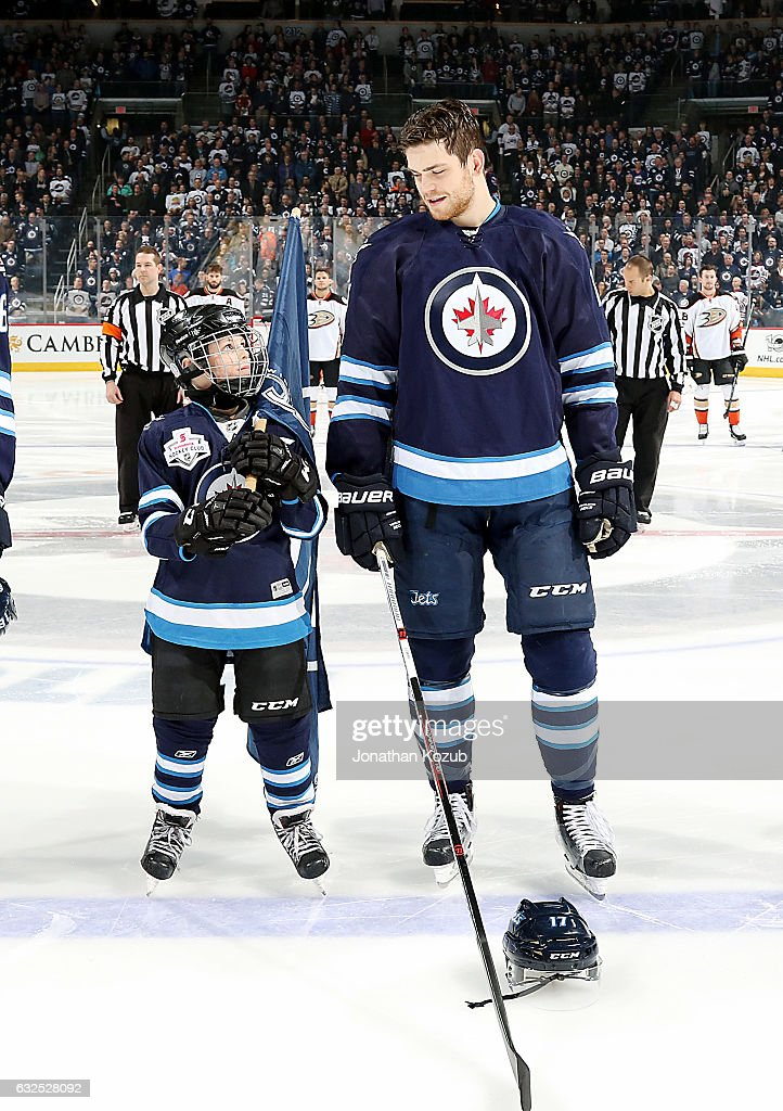 Adam Lowry #17 of the Winnipeg Jets shares a smile with the ScotiaBank Skater prior to puck drop against the Anaheim Ducks at the MTS Centre on January 23, 2017 in Winnipeg, Manitoba, Canada.