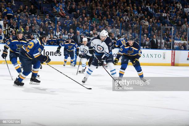 Adam Lowry of the Winnipeg Jets skates against Alexander Steen of the St Louis Blues on January 31 2017 at Scottrade Center in St Louis Missouri