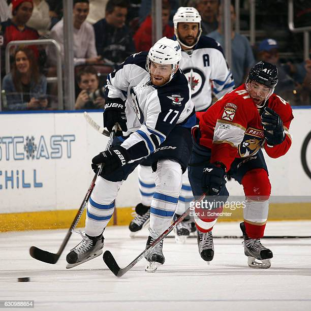 Adam Lowry of the Winnipeg Jets skates for possession against Greg McKegg of the Florida Panthers at the BBT Center on January 4 2017 in Sunrise...