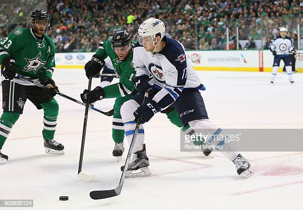 Adam Lowry of the Winnipeg Jets skates the puck against Radek Faksa of the Dallas Stars in the second period at American Airlines Center on January 7...