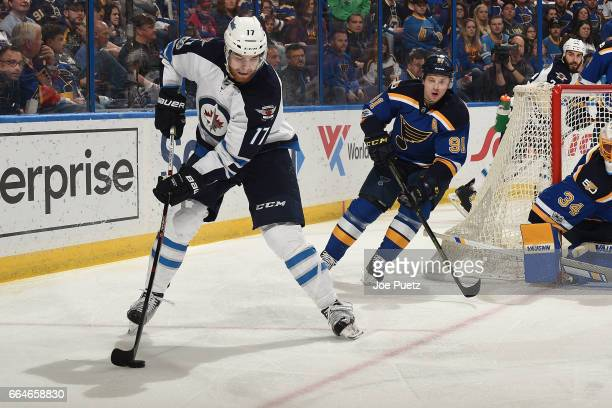 Adam Lowry of the Winnipeg Jets skates with the puck as Vladimir Tarasenko of the St Louis Blues defends on April 4 2017 at Scottrade Center in St...