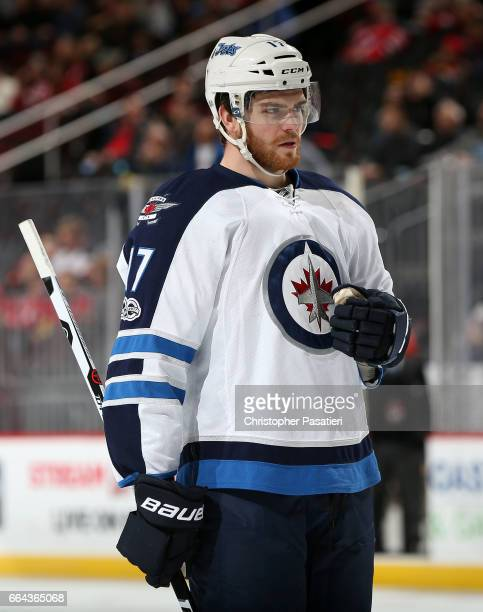 Adam Lowry of the Winnipeg Jets skates with the puck during the first period against the New Jersey Devils on March 28 2017 at the Prudential Center...