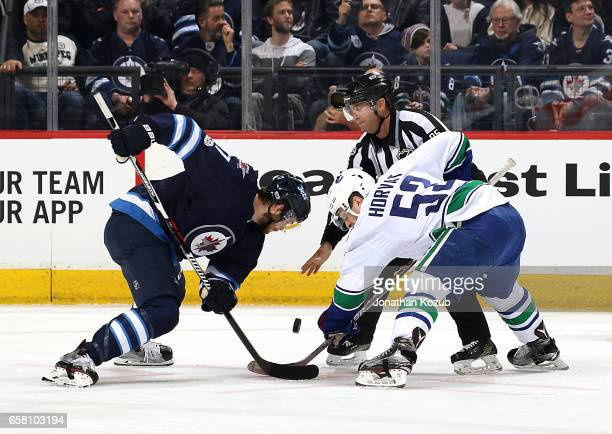 Adam Lowry of the Winnipeg Jets takes a first period faceoff against Bo Horvat of the Vancouver Canucks at the MTS Centre on March 26 2017 in...