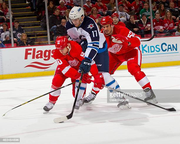 Adam Lowry of the Winnipeg Jets tries to stick handle with the puck in between Stephen Weiss and Jonathan Ericsson of the Detroit Red Wings during a...