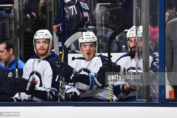 Adam Lowry Stephen Gibson and Chris Thorburn of the Winnipeg Jets sit on the bench during the second period of a game against the Columbus Blue...