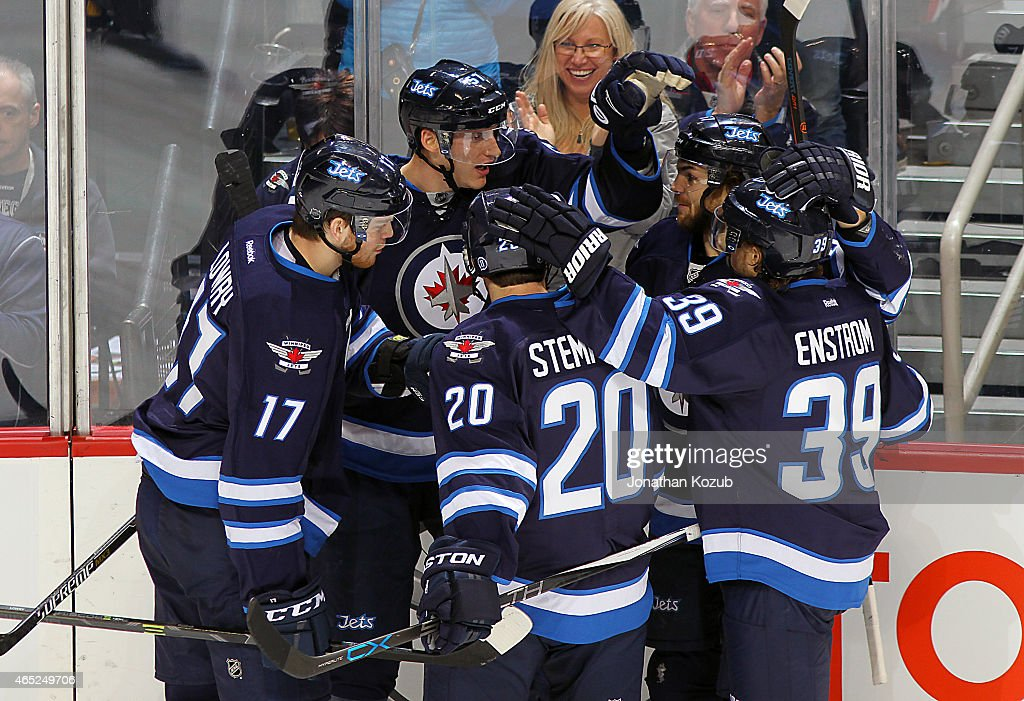 Adam Lowry #17, Tyler Myers #57, Lee Stempniak #20, Michael Frolik #67 and Toby Enstrom #39 of the Winnipeg Jets celebrate a third period goal against the Ottawa Senators on March 4, 2015 at the MTS Centre in Winnipeg, Manitoba, Canada.