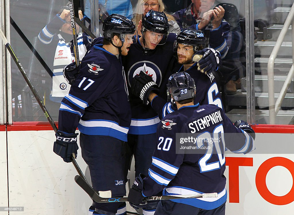 Adam Lowry #17, Tyler Myers #57, Toby Enstrom #39 and Lee Stempniak #20 of the Winnipeg Jets celebrate a third period goal against the Ottawa Senators on March 4, 2015 at the MTS Centre in Winnipeg, Manitoba, Canada.
