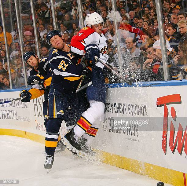 Adam Mair of the Buffalo Sabres checks Dennis Seidenberg of the Florida Panthers on November 18 2009 at HSBC Arena in Buffalo New York Behind them is...