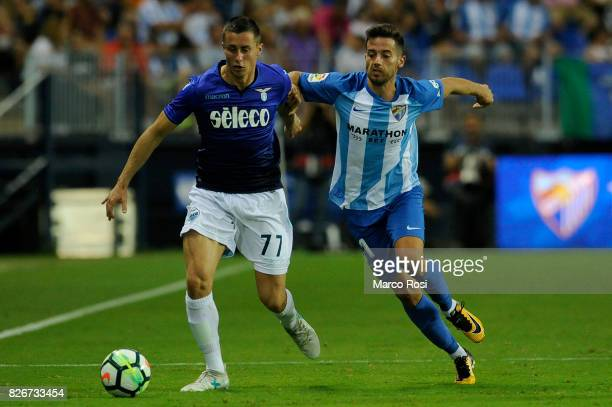Adam Marusic of SS Lazio compete for the ball with Jony of Malaga CF during the PreSeason Friendly match between Malaga CF and SS Lazio at Estadio La...