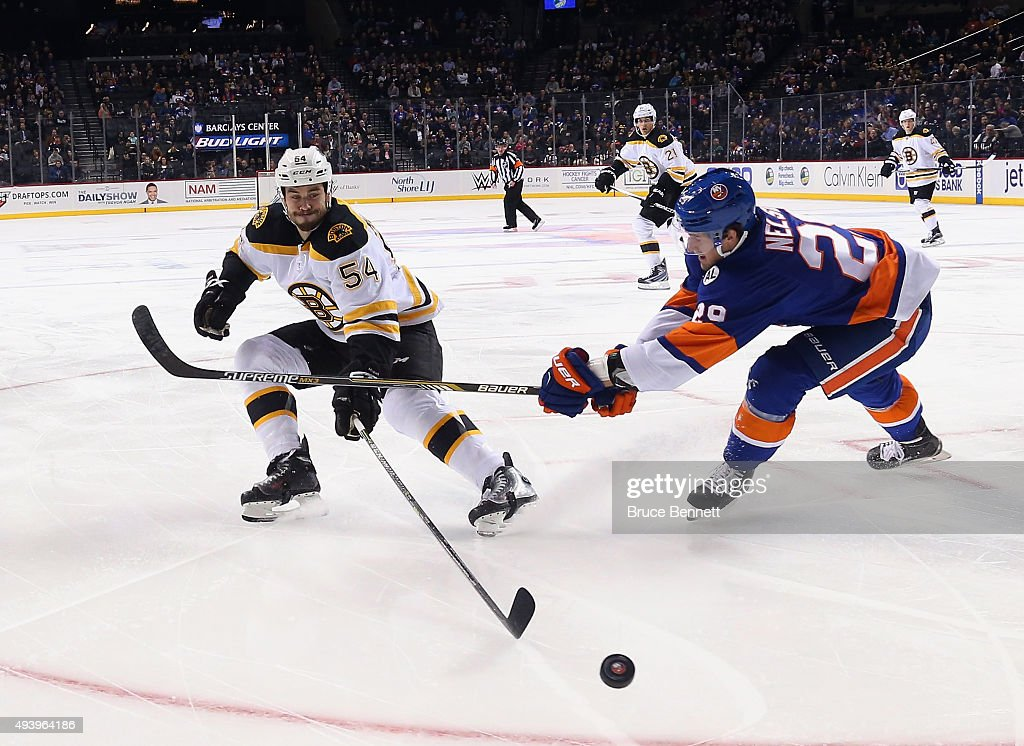 Adam McQuaid #54 of the Boston Bruins and Brock Nelson #29 of the New York Islanders pursue the puck during the first period at the Barclays Center on October 23, 2015 in the Brooklyn borough of New York City.