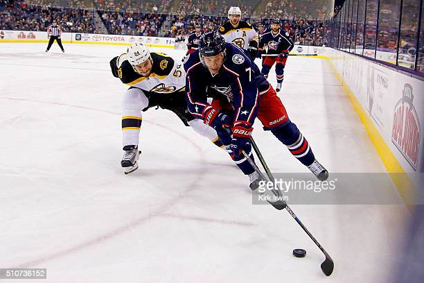 Adam McQuaid of the Boston Bruins and Jack Johnson of the Columbus Blue Jackets battle for control of the puck during the second period on February...