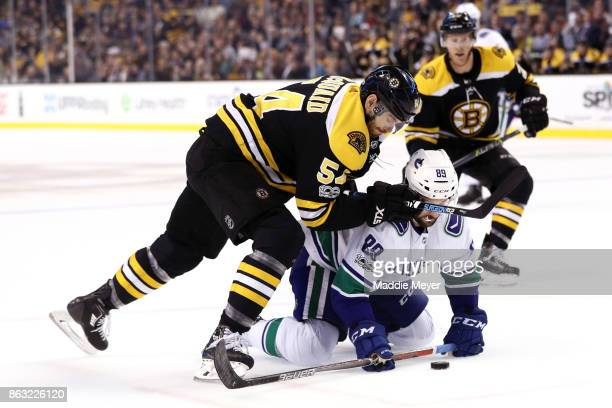 Adam McQuaid of the Boston Bruins and Sam Gagner of the Vancouver Canucks battle for control of the puck during the second period at TD Garden on...