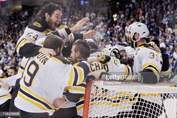 Adam McQuaid of the Boston Bruins celebrates with his teammates Brad Marchand Tyler Seguin Tim Thomas and Zdeno Chara after defeating the Vancouver...