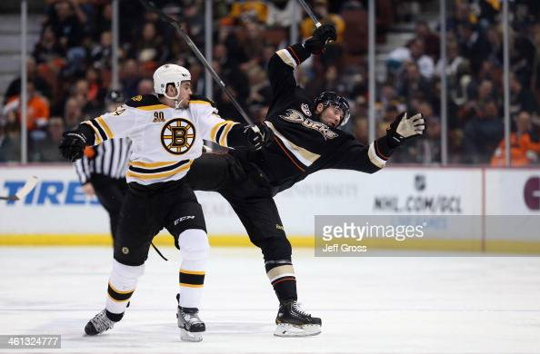 Adam McQuaid of the Boston Bruins checks Patrick Maroon of the Anaheim Ducks in the first period at Honda Center on January 7 2014 in Anaheim...